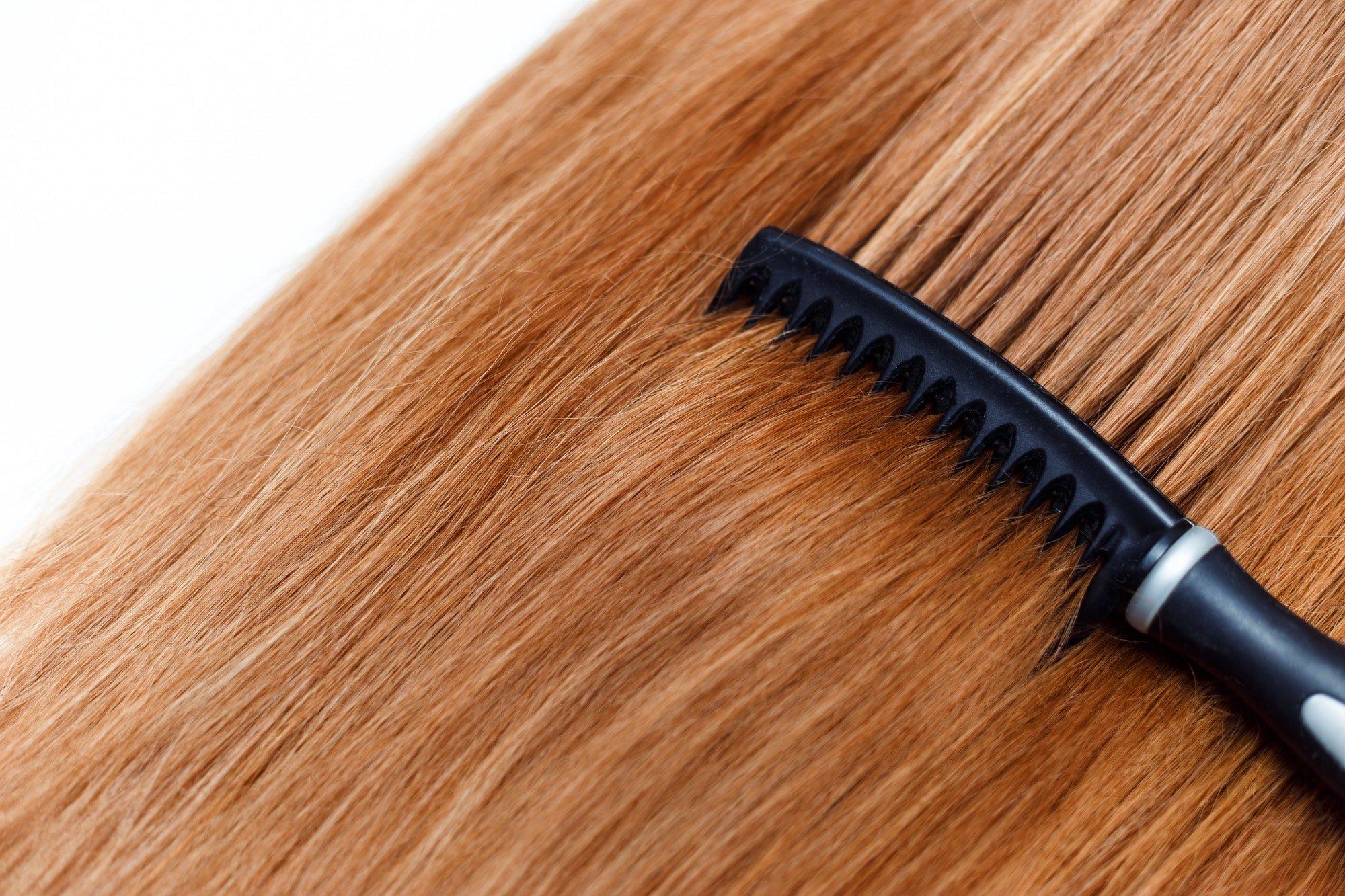 Black hairbrush comb straight red hair on white
