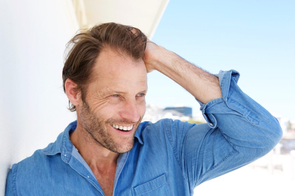 Close up attractive male model smiling with hand in hair