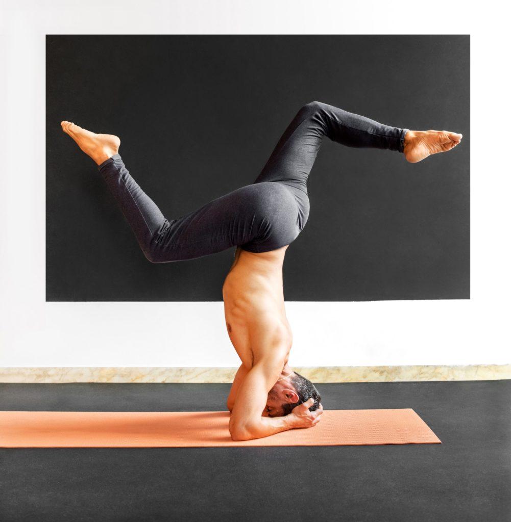 Man doing a sirsasana variation yoga headstand