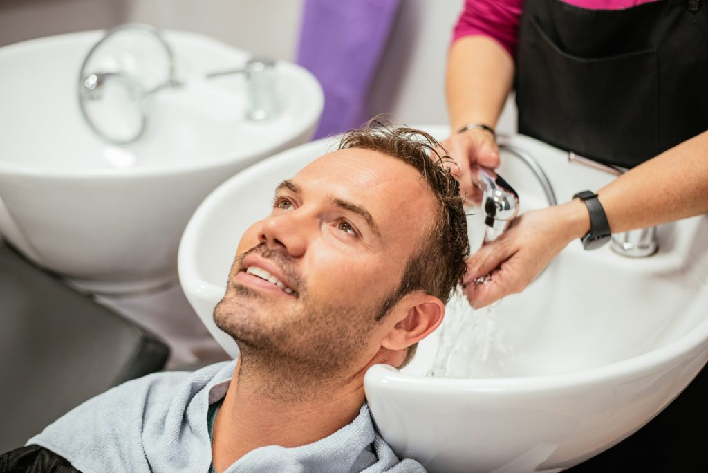 Man having his hair washed in a barbershop