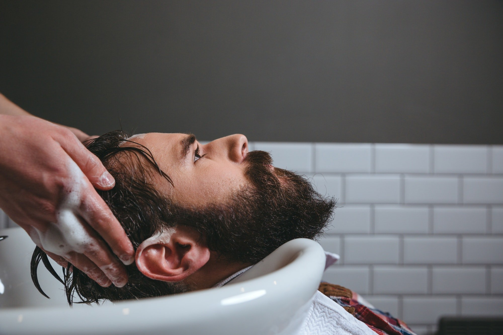 Barber washing client's hair